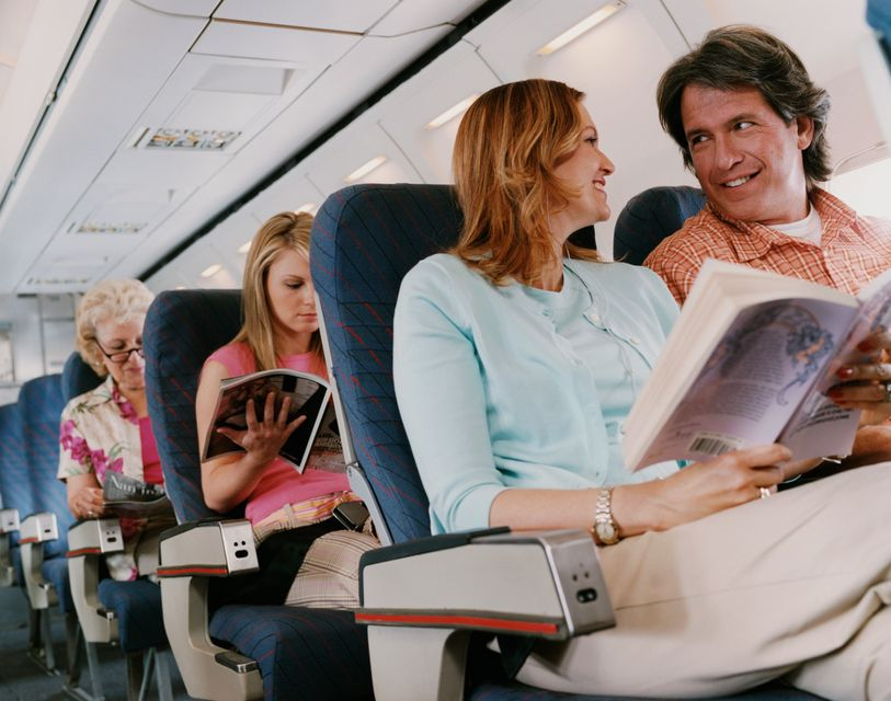 A couple talking to each other on a flight