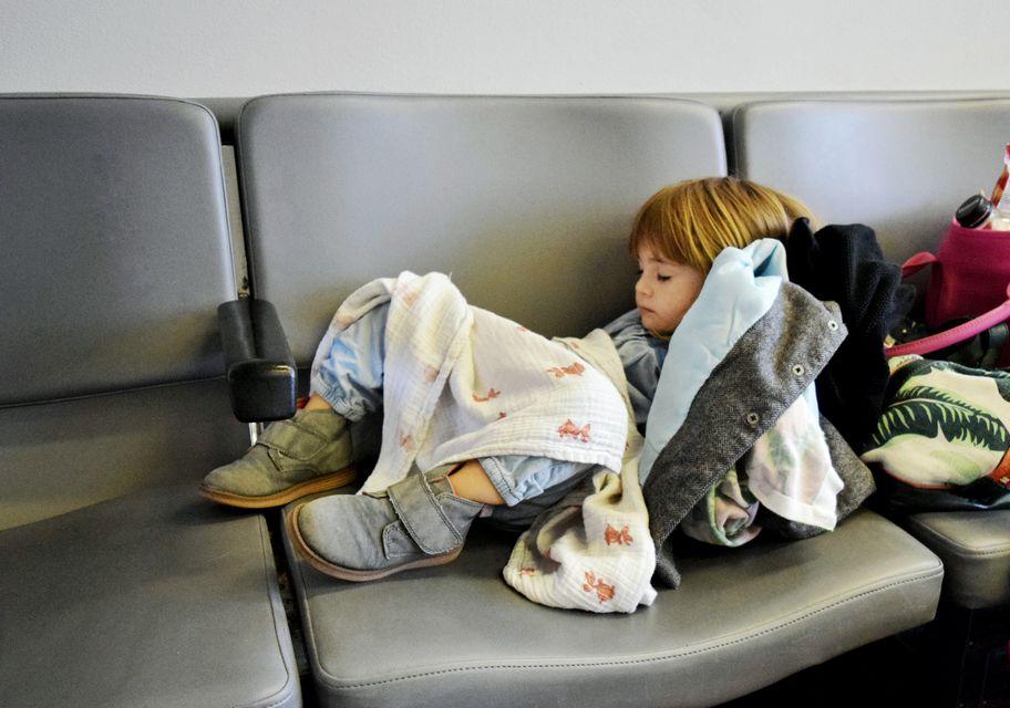 Μικρό παιδί κοιμάται στα καθίσματα αίθουσας αναμονής αεροδρομίου