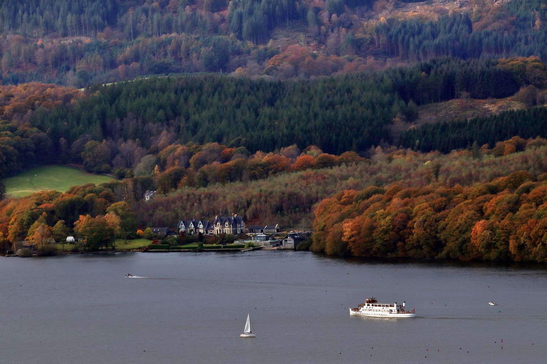 Boats sailing on Lake Windermere, with autumn leaves on the shore