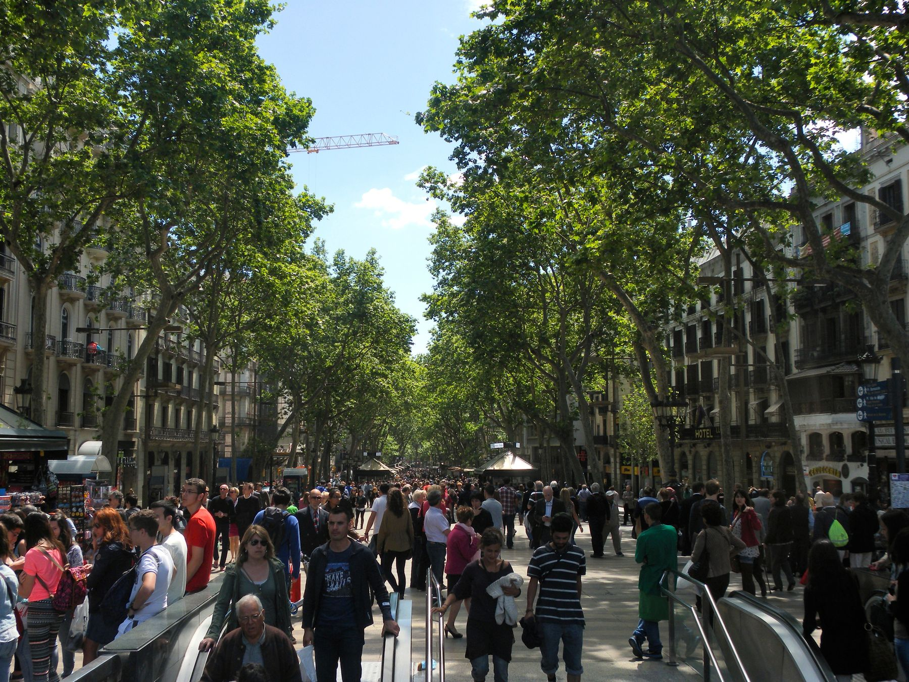 Daytime view of Las Ramblas, crowded with people and lined by trees and buildings