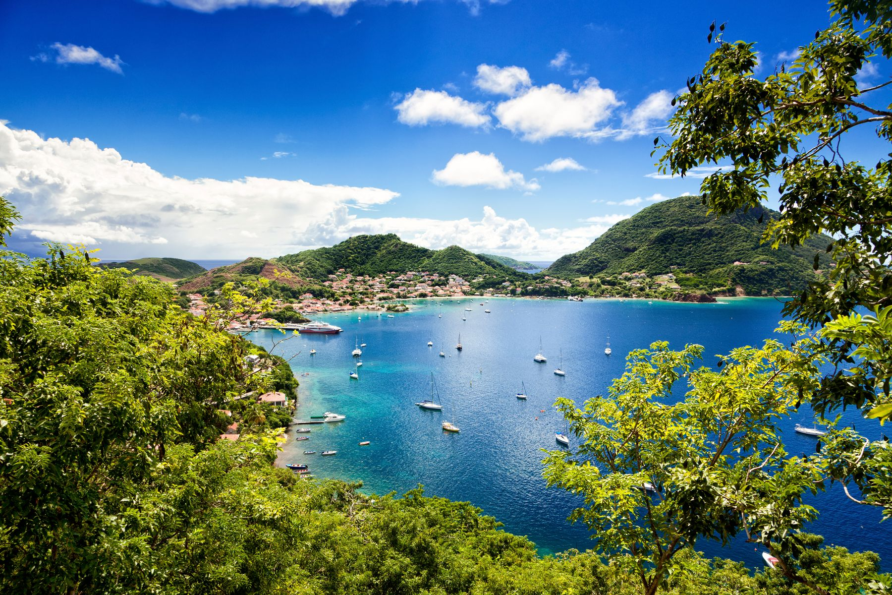 a picturesque bay of water surrounded by lush green mountains, a great sunny destination for a December vacation