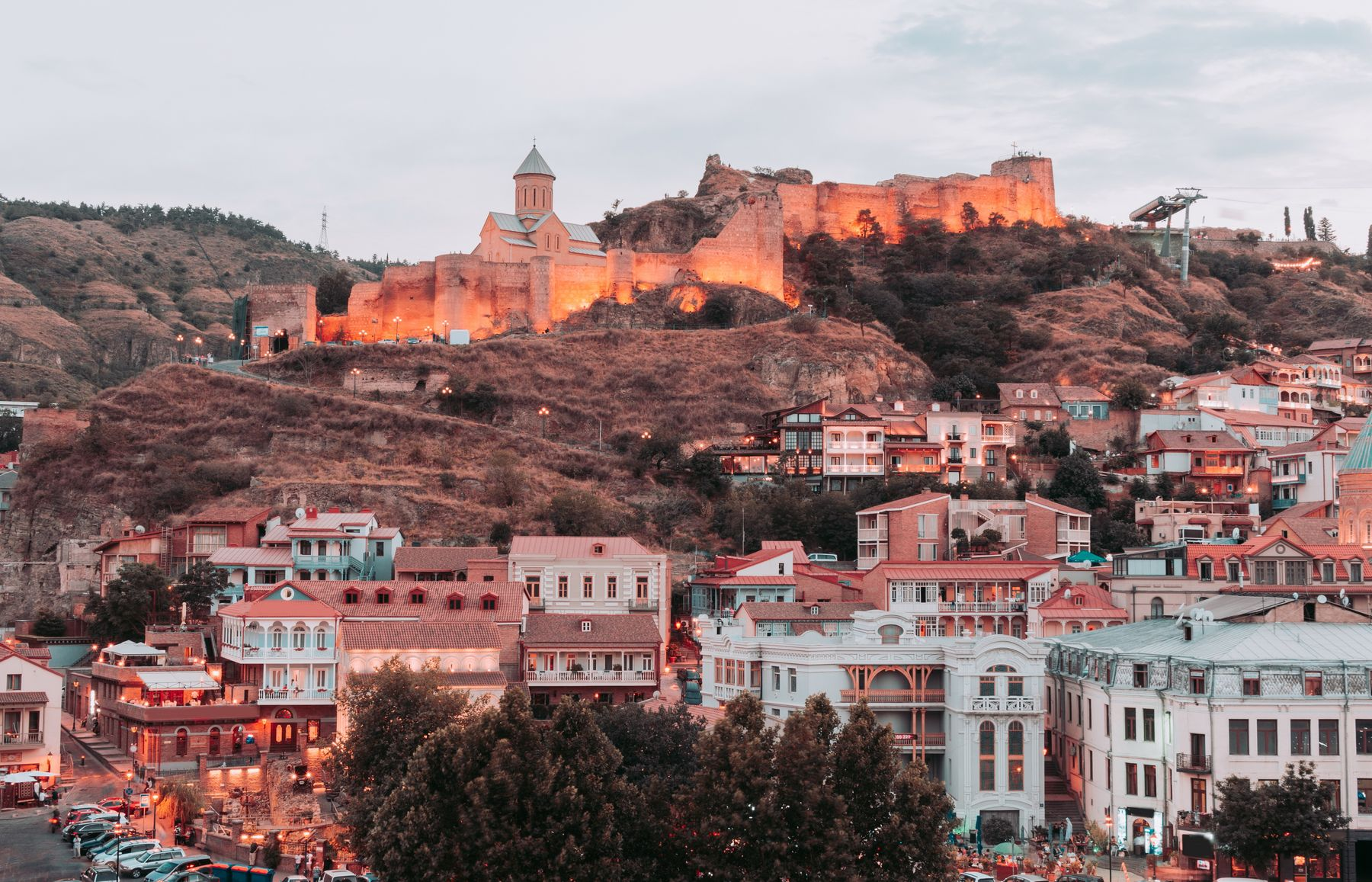 Photo shows the skyline of Tblisi, Georgia (one of our unexected destinations) at dusk, with its white and terraccotta coloured buildings