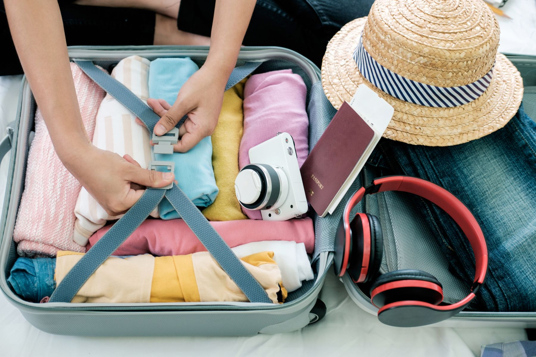 Suitcase filled with rolled items of clothing, with a passport, sun hat and earphones beside it. Someone is securing the clasps.