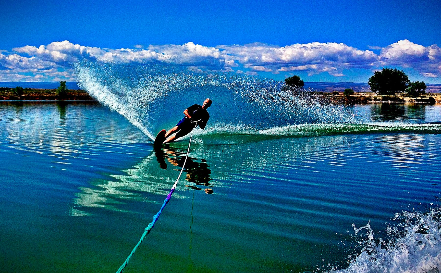 man water skiing with large wave