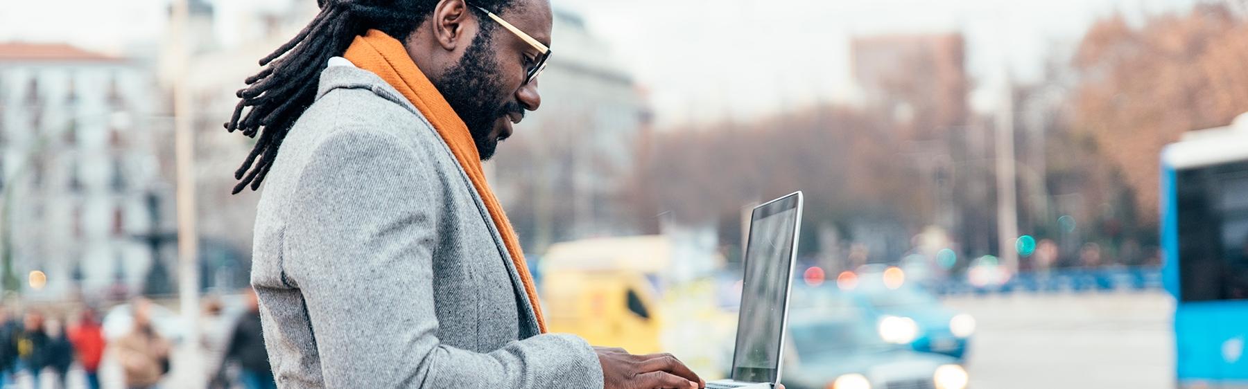 Viajante usando seu notebook em uma área pública, pesquisando sobre como planejar uma viagem.