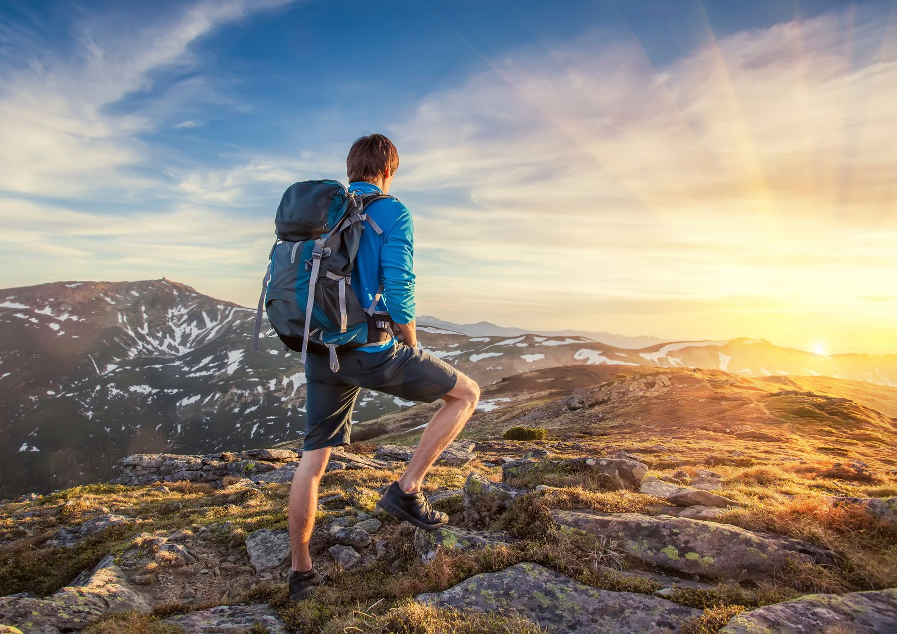 Man standing on a hill, getting ready to explore: something we can look forward to if we plan a trip a year in advance