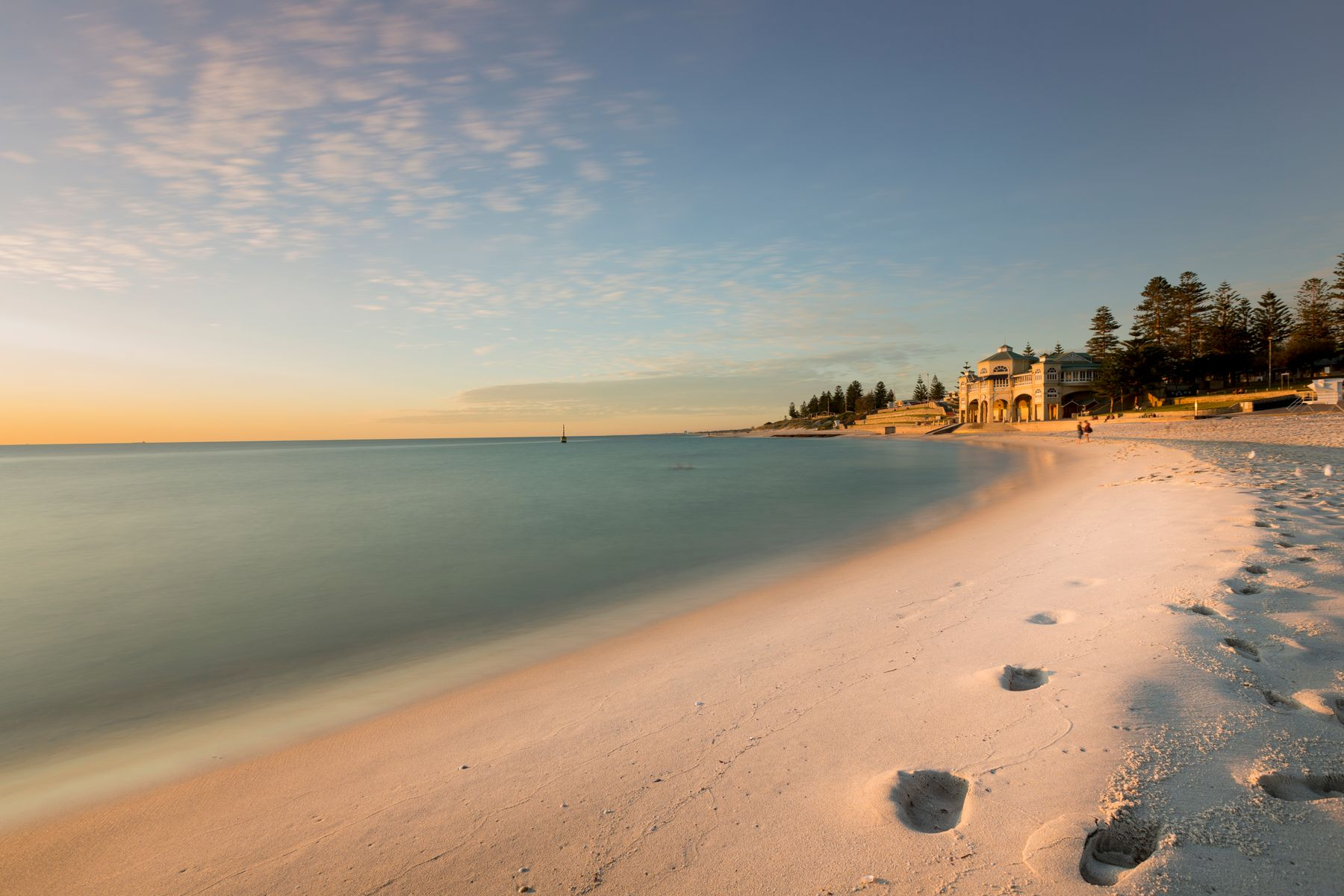 Footprints along the white sand near the water on Cottesloe Beach, Australia