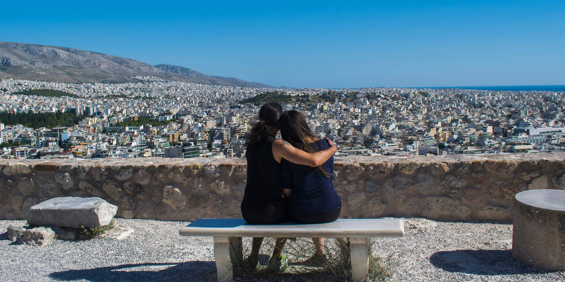 Two people on a bench hugging looking over a Greek city