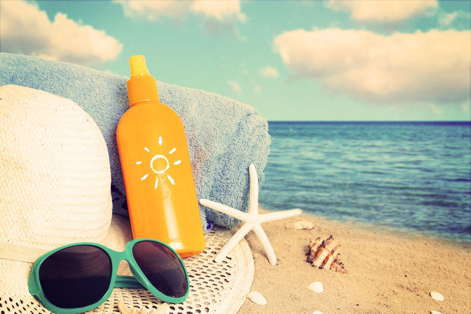 Bottle of suntan lotion, glasses, hat and towel on the beach