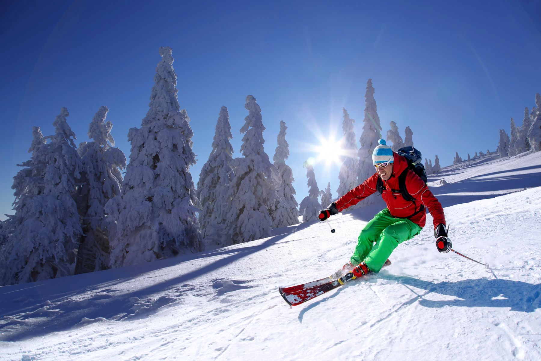 A skier smiles as they hug a curve downhill on a sunny day. Evergreens blanketed in snow form the backdrop.