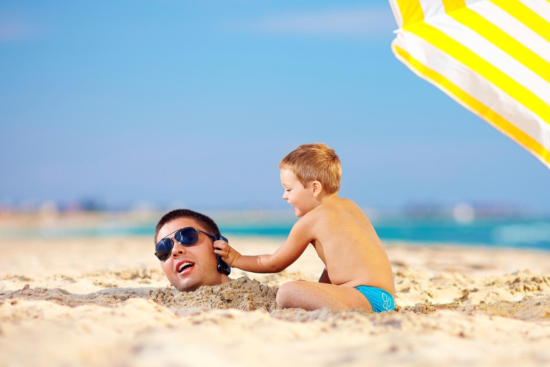 Vater und Sohn in den Sommerferien am Strand