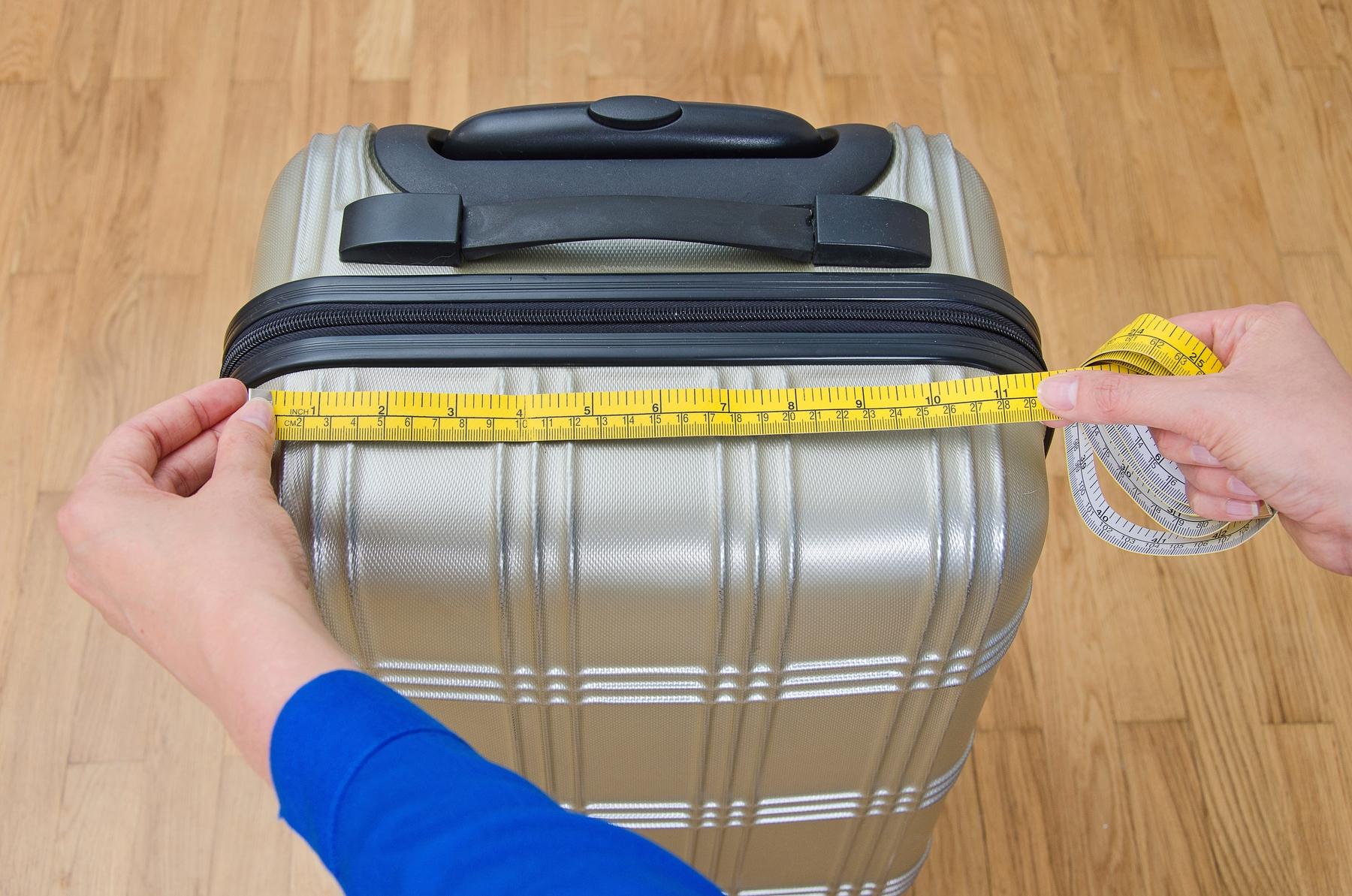 Pessoa com fita métrica medindo tamanho da mala