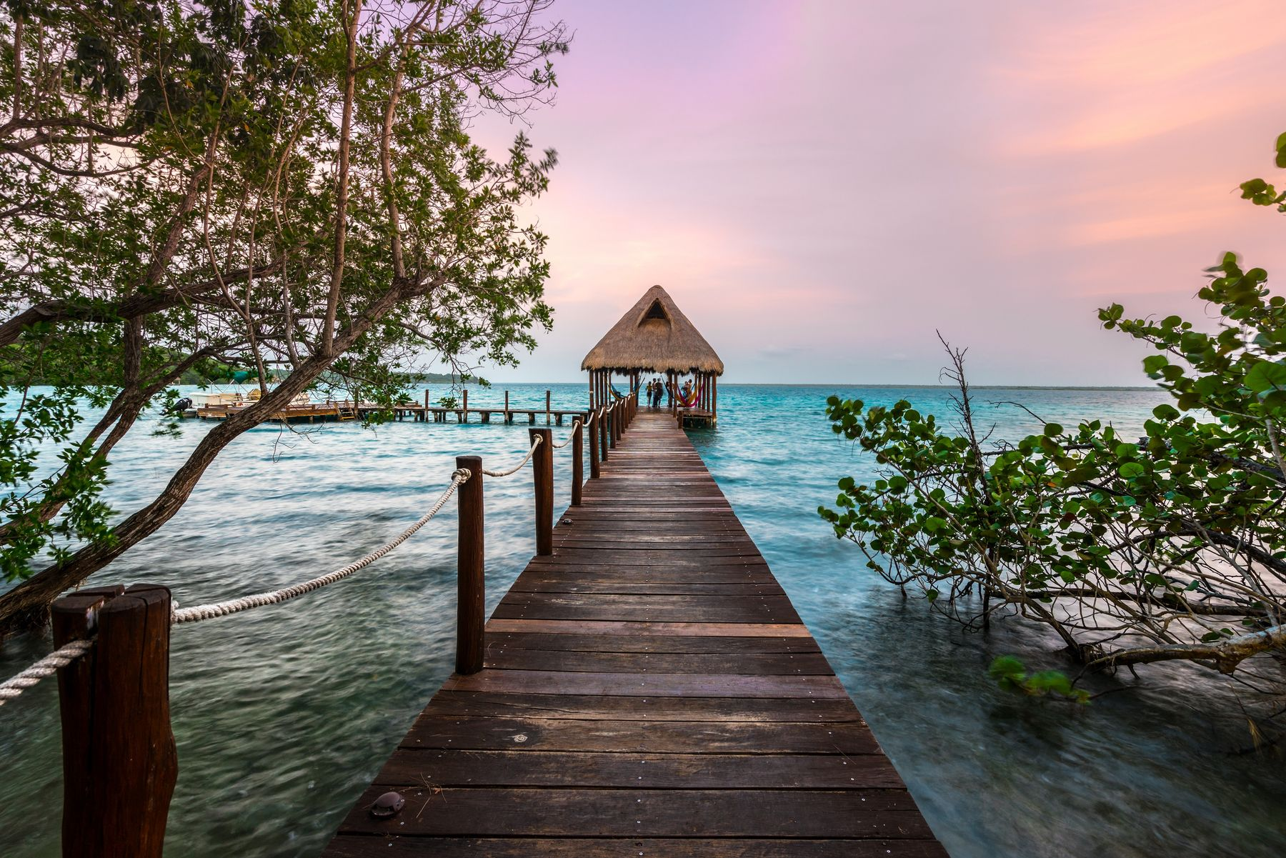 Sunset sky with dock leading to a cabana in Mexico