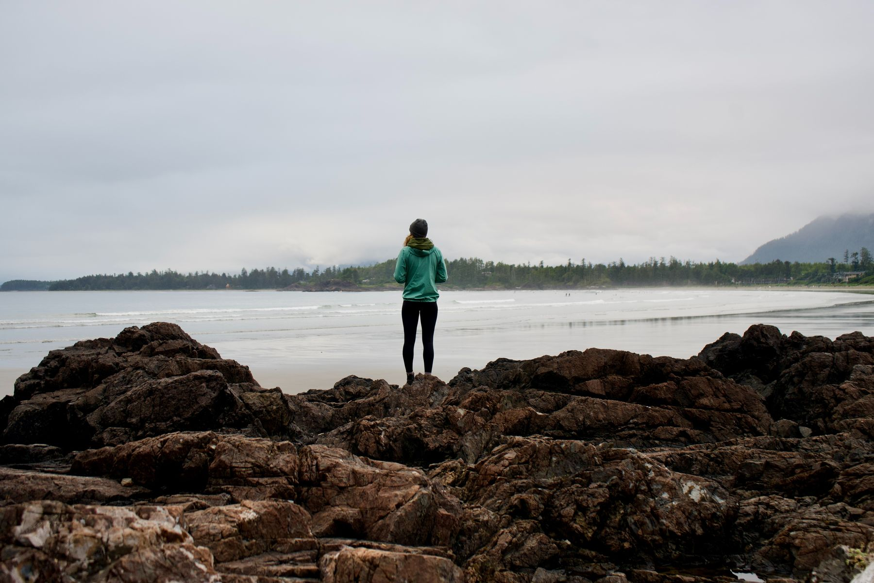 woman standing on rocks by the coast in Tofino, BC, a top beach vacation destination in North America