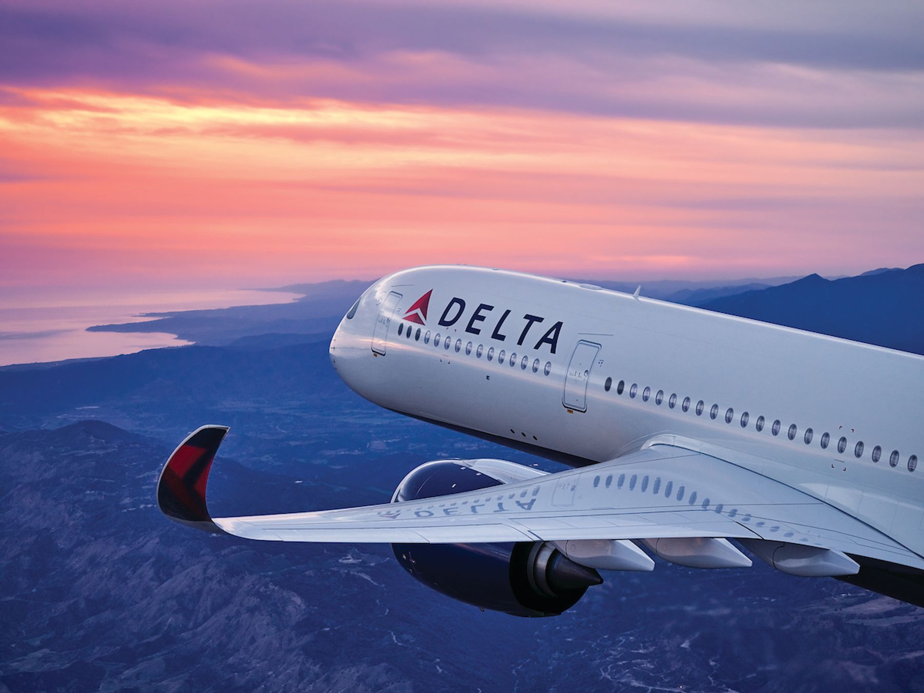 A Delta airlines plane crosses an orange and blue sky