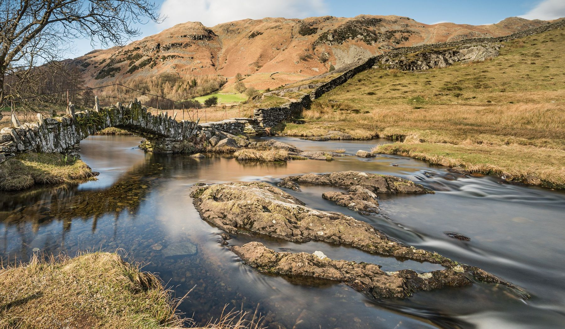 Slater bridge in the Lake District, an old stone bridge spanning a calm river in remote countryside
