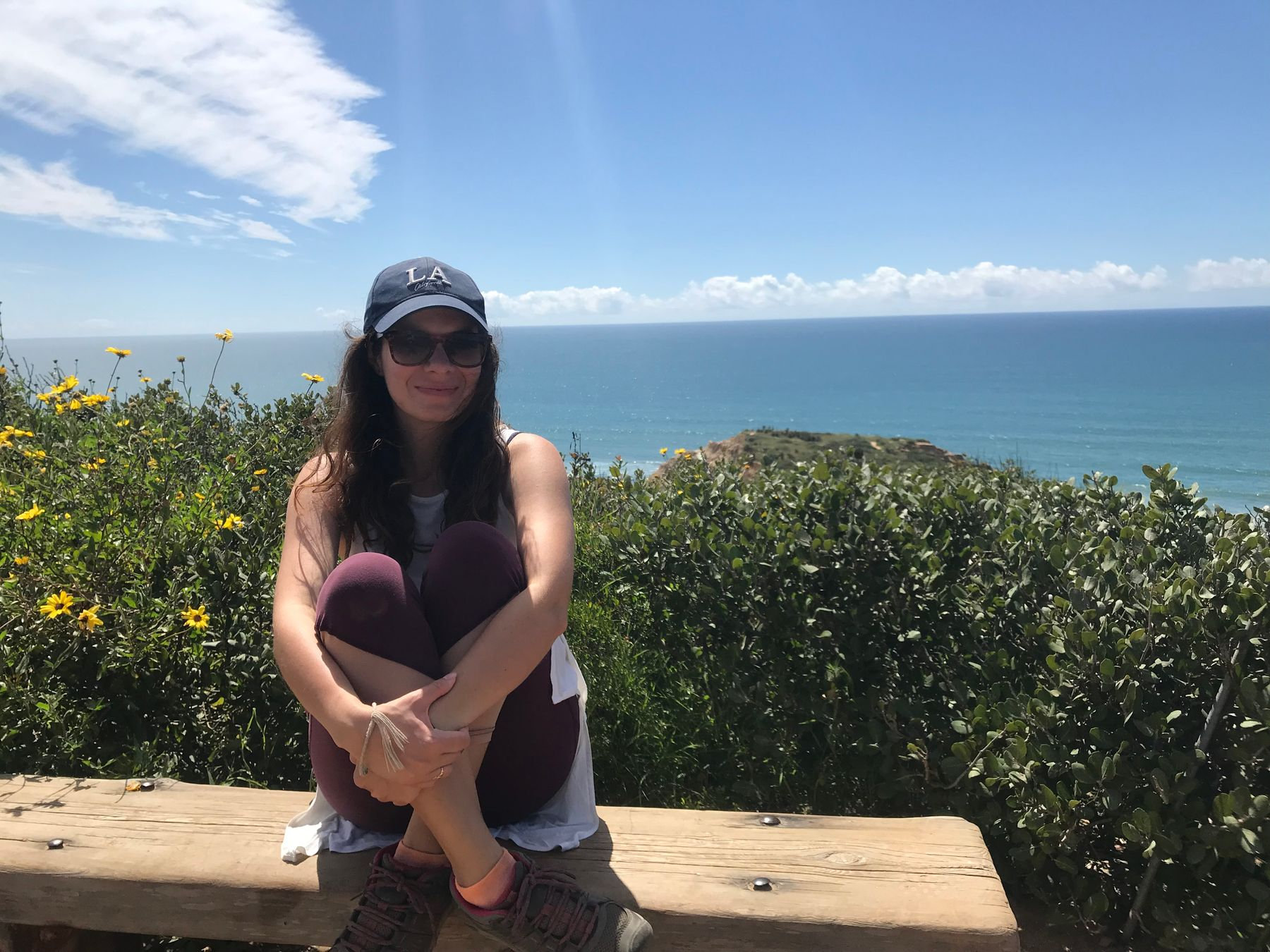 solo traveller wearing a hat and sunglasses sitting on a bench at Torrey Pines National Park in San Diego, California