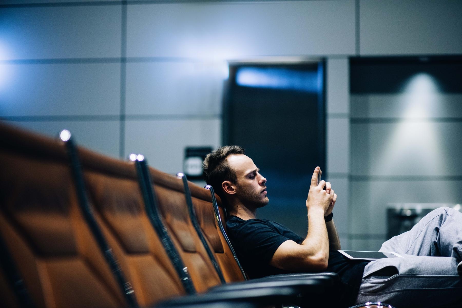 Homem no aeroporto mexe no celular