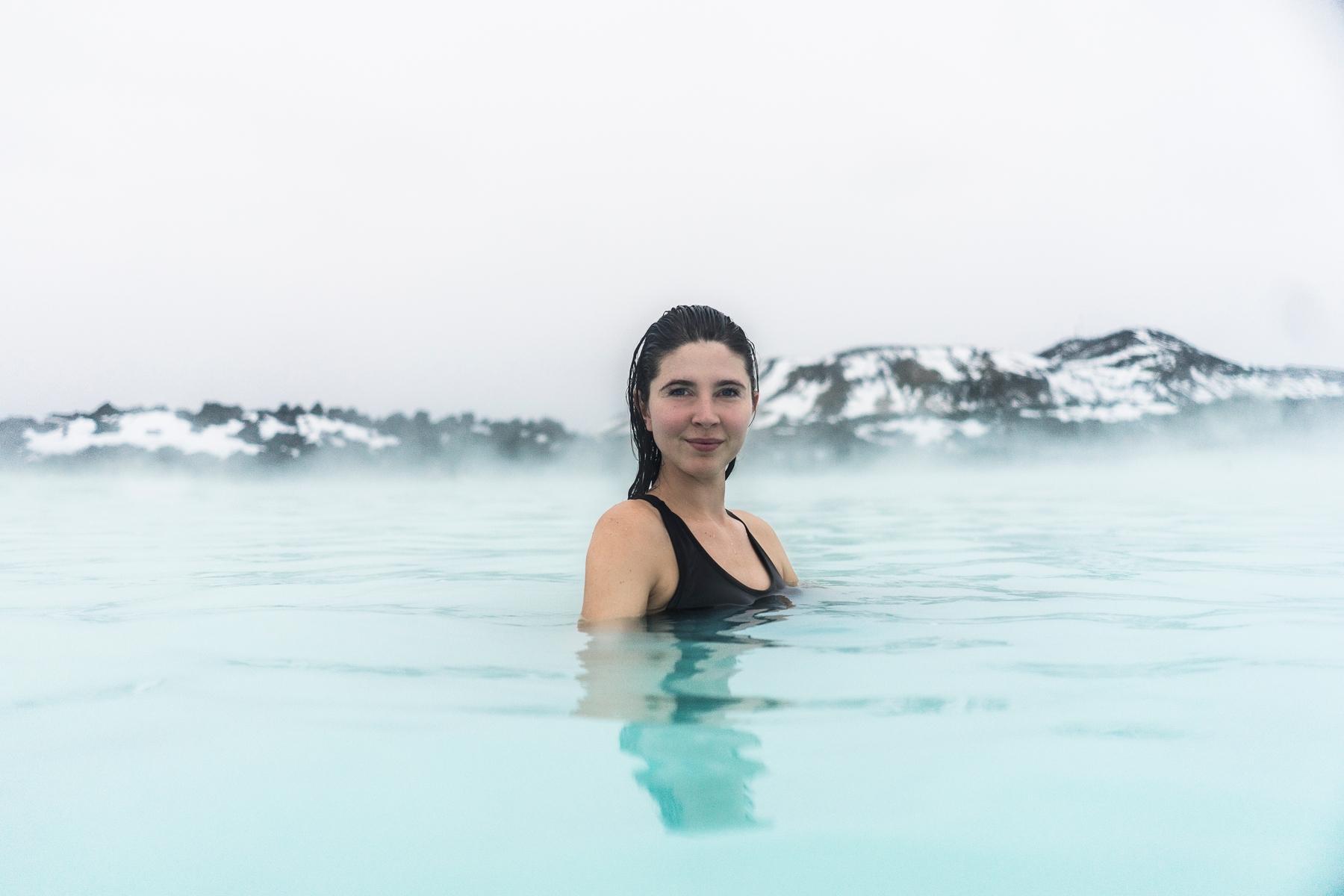 Девушка плавает в Голубой лагуне в Исландии. В этой стране удивительные места повсюду!