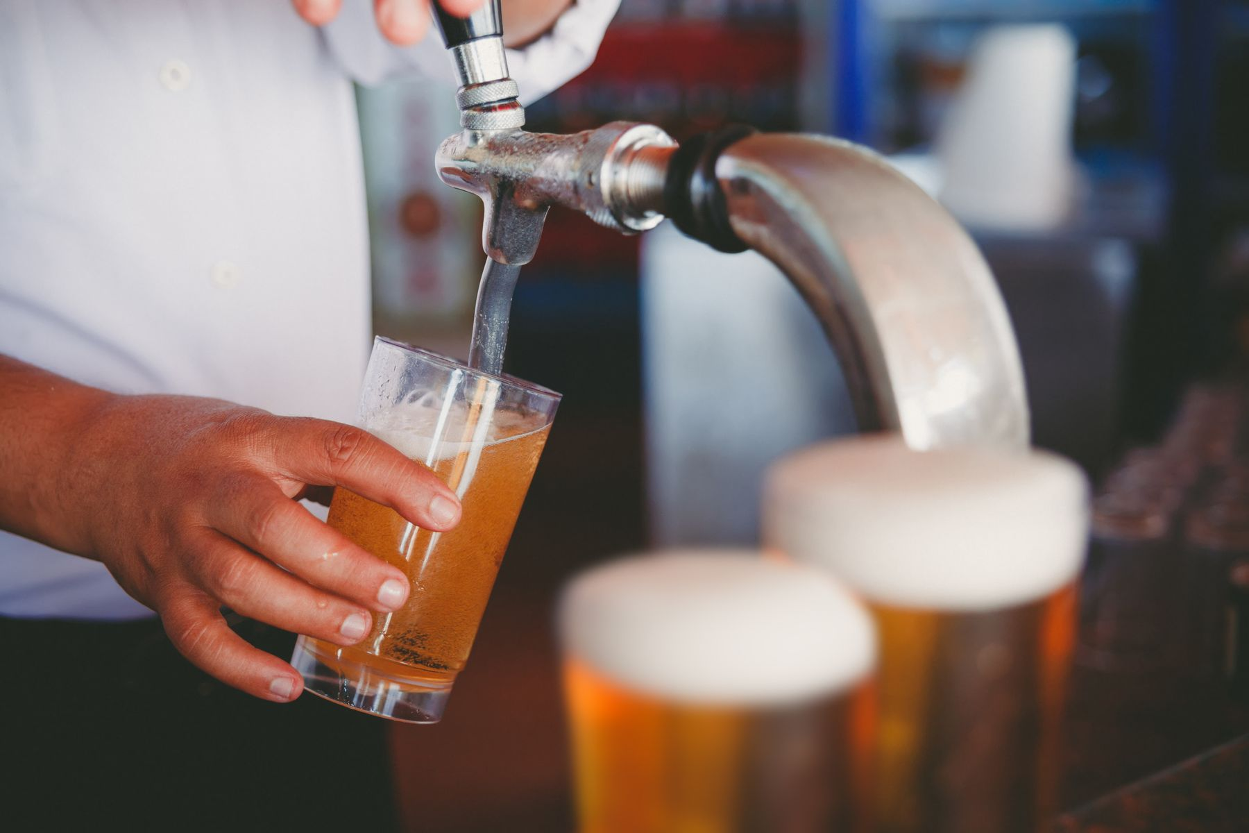 bartender pouring pints of beer on tap