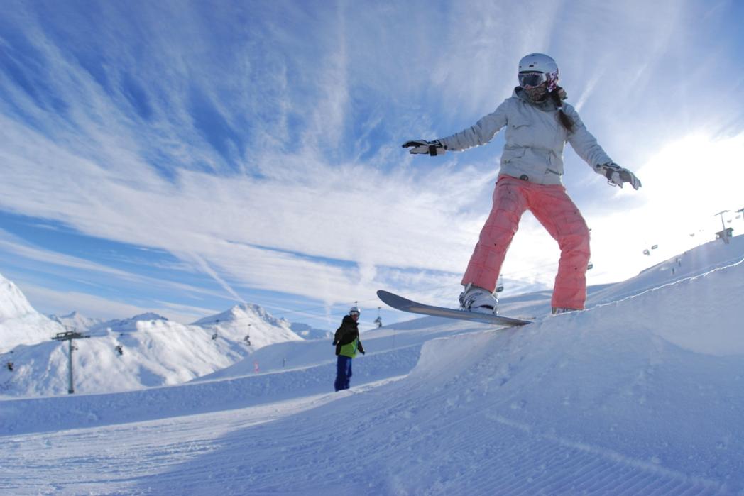 Γυναίκα που κάνει snowboard σε χιονισμένο βουνό.