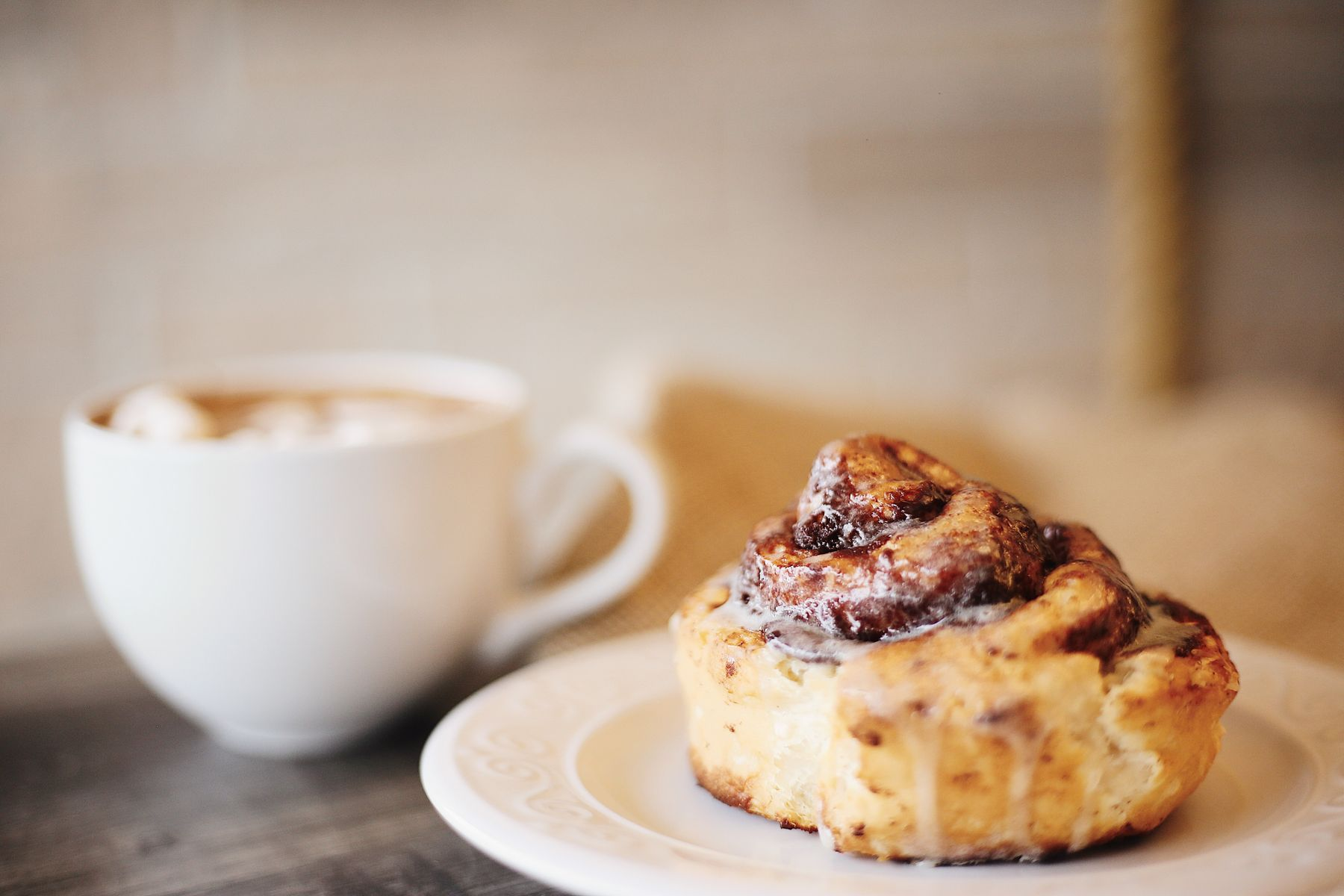 cinnamon roll on a plate with a latte in the background