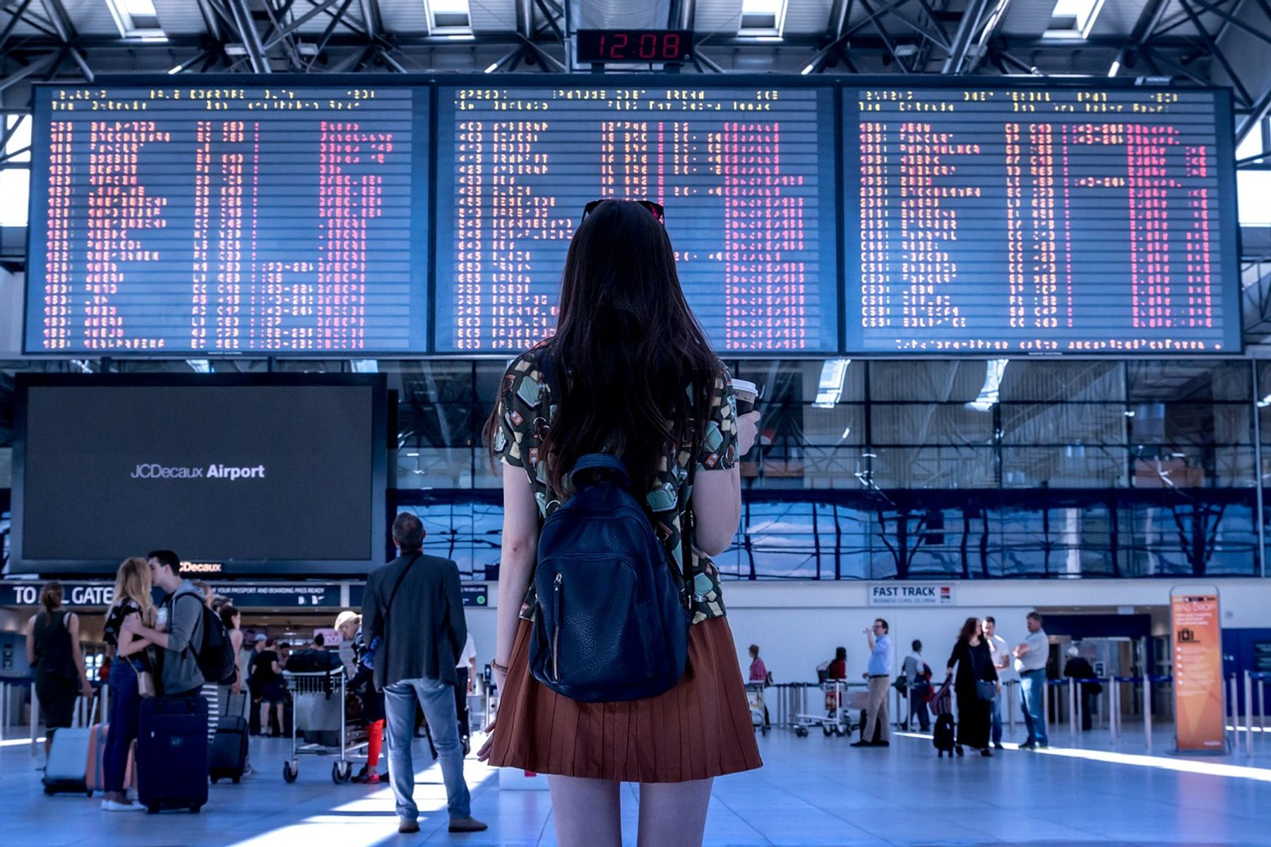 Woman standing at airport checking the departure board.