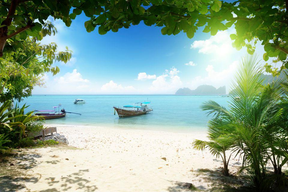 Βάρκα σε παραλία φαίνεται μέσα απ' την πλούσια βλάστηση με τον ήλιο να αστράφτει, Κράμπι. Χαρακτηριστική εικόνα σ' ένα ταξίδι στην Ταϊλάνδη