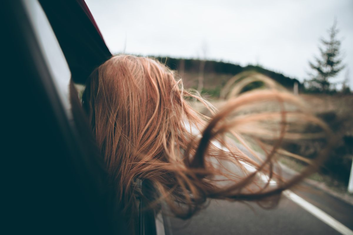 Woman with her hair flying out the window of a car. Use our car rental hacks to save money.