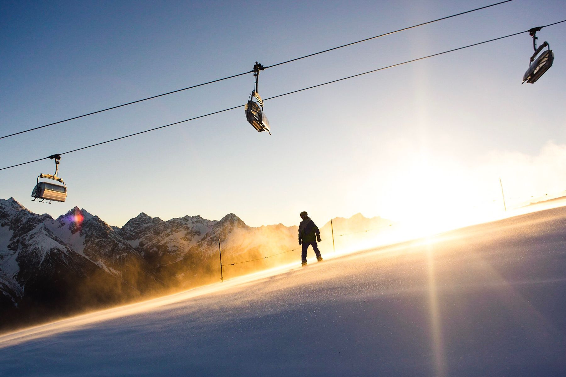 A skiier on a slope beneath a cablecar, with the sun setting behind them