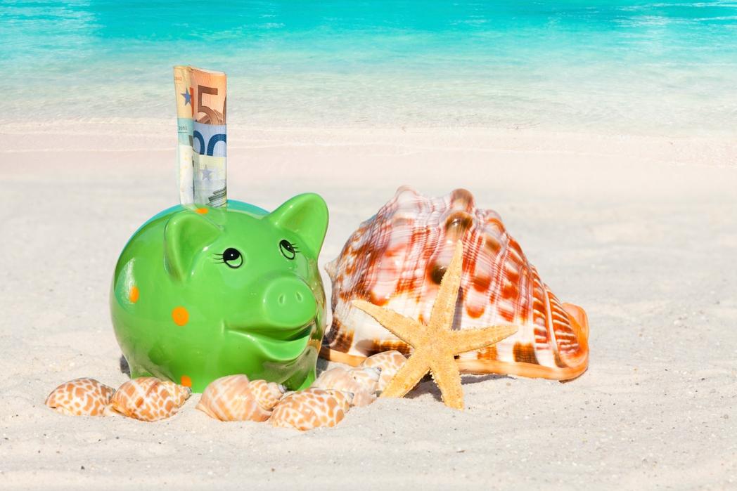Γουρουνάκι με ευρώ δίπλα σε κοχύλια σε παραλία
