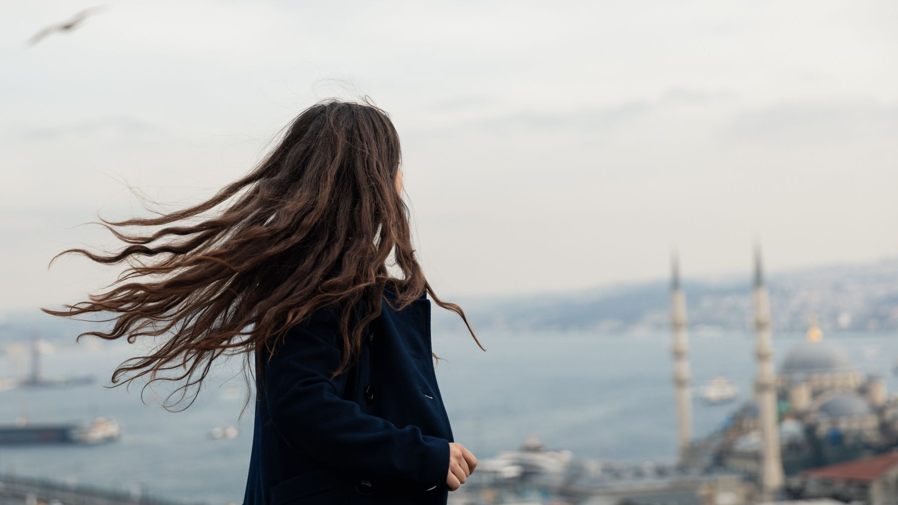 Young woman looking out over Istanbul, the wind whipping her hair.