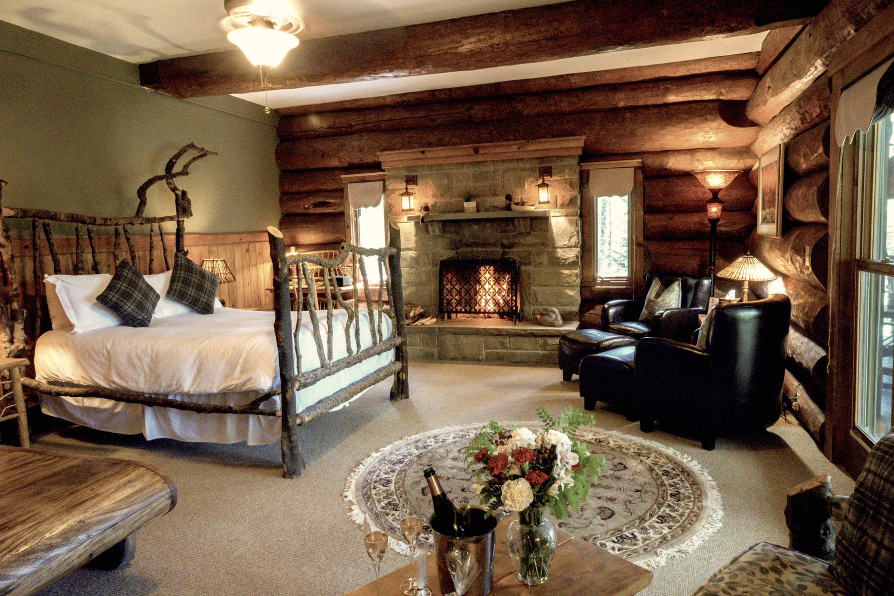 cozy suite in Trout Point Lodge. Bed, fireplace, table with a bottle of champagne and two glasses poured.