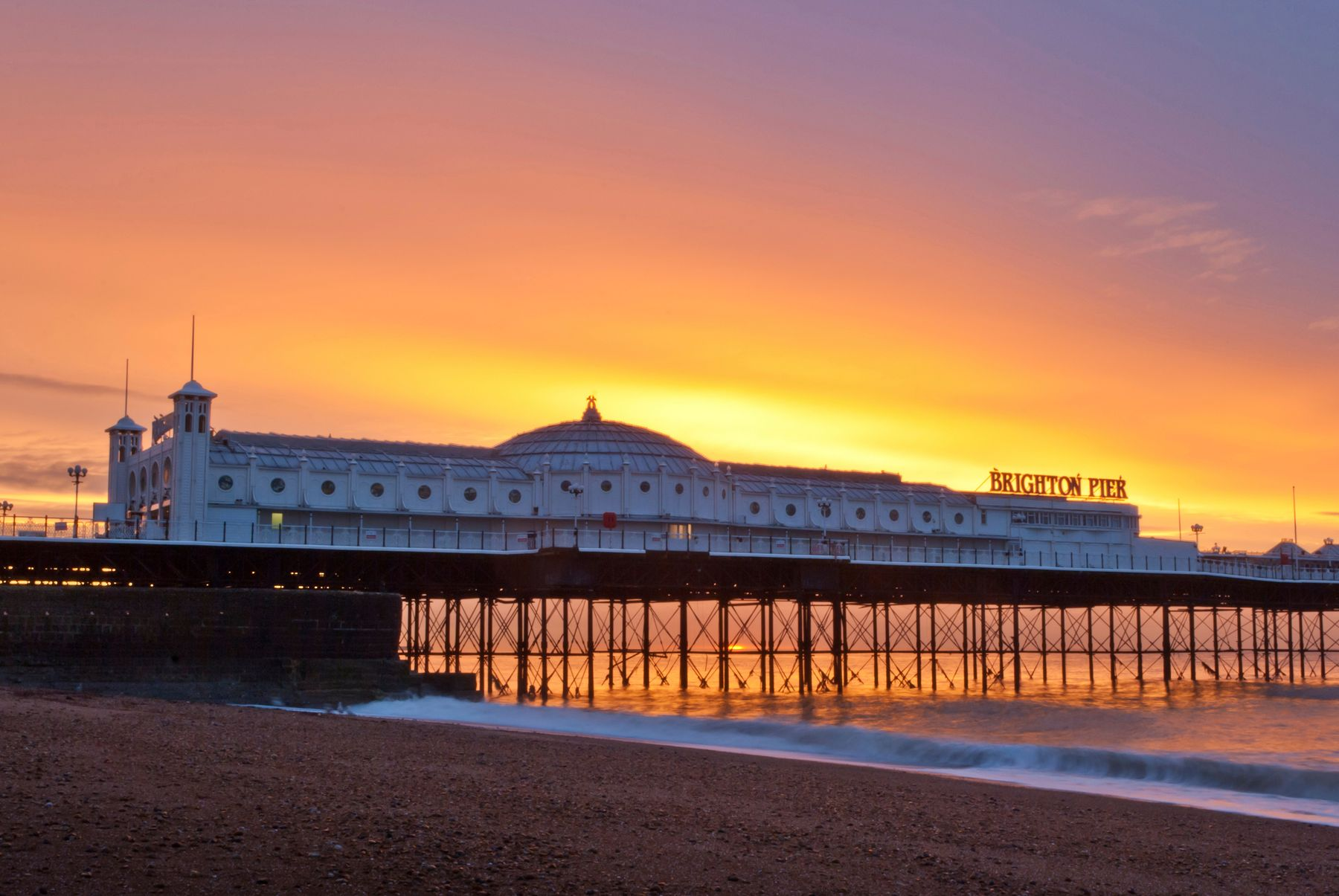 A view of Brighton pier from the beach at sunset