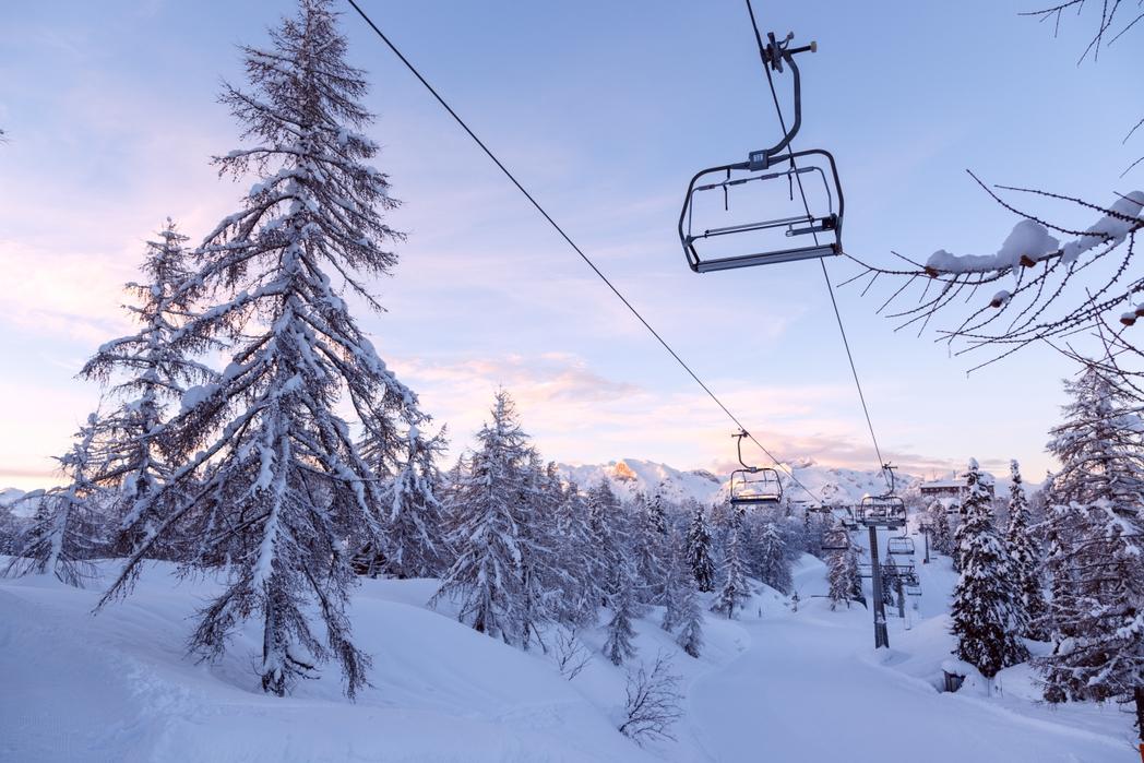 Χιονισμένο τοπίο με έλατα και η εικόνα ενός lift χιονοδρομικού.