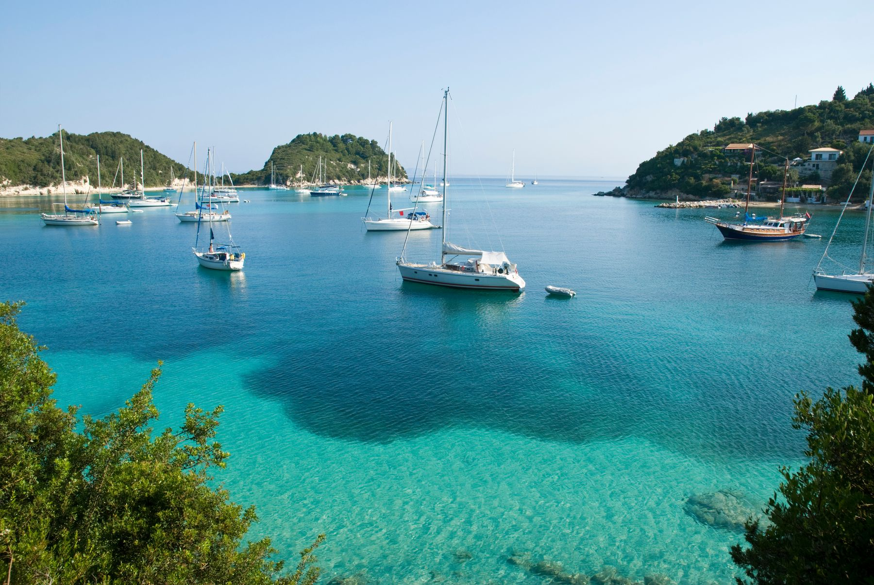 Yachts resting in the turquoise waters of Greece. Sailing is one of the best adventure holidays in the UK and abroad