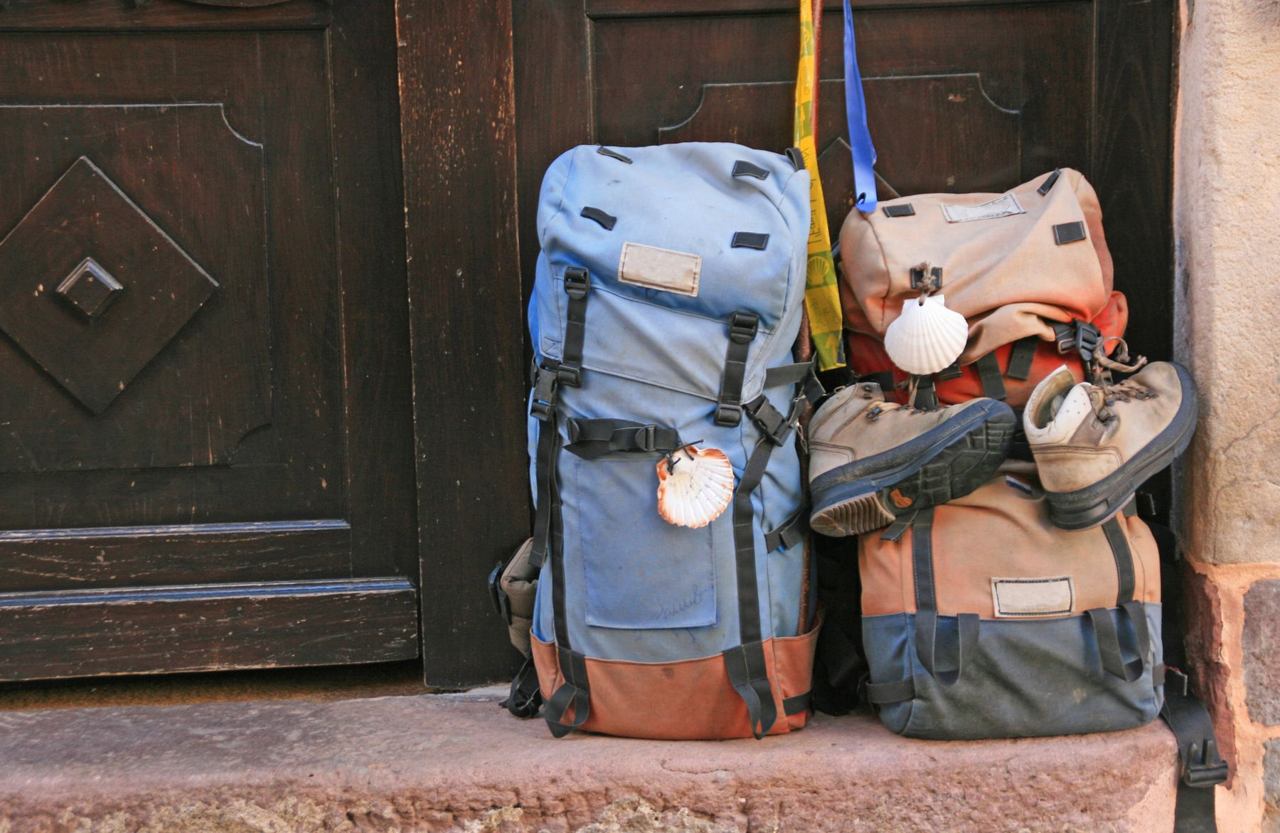 Two large backpacks lean against a wooden door. They are small enough to avoid Delta baggage fees.