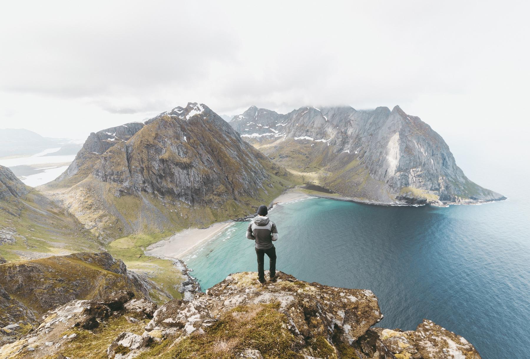 man standing on mountain top overlooking bay