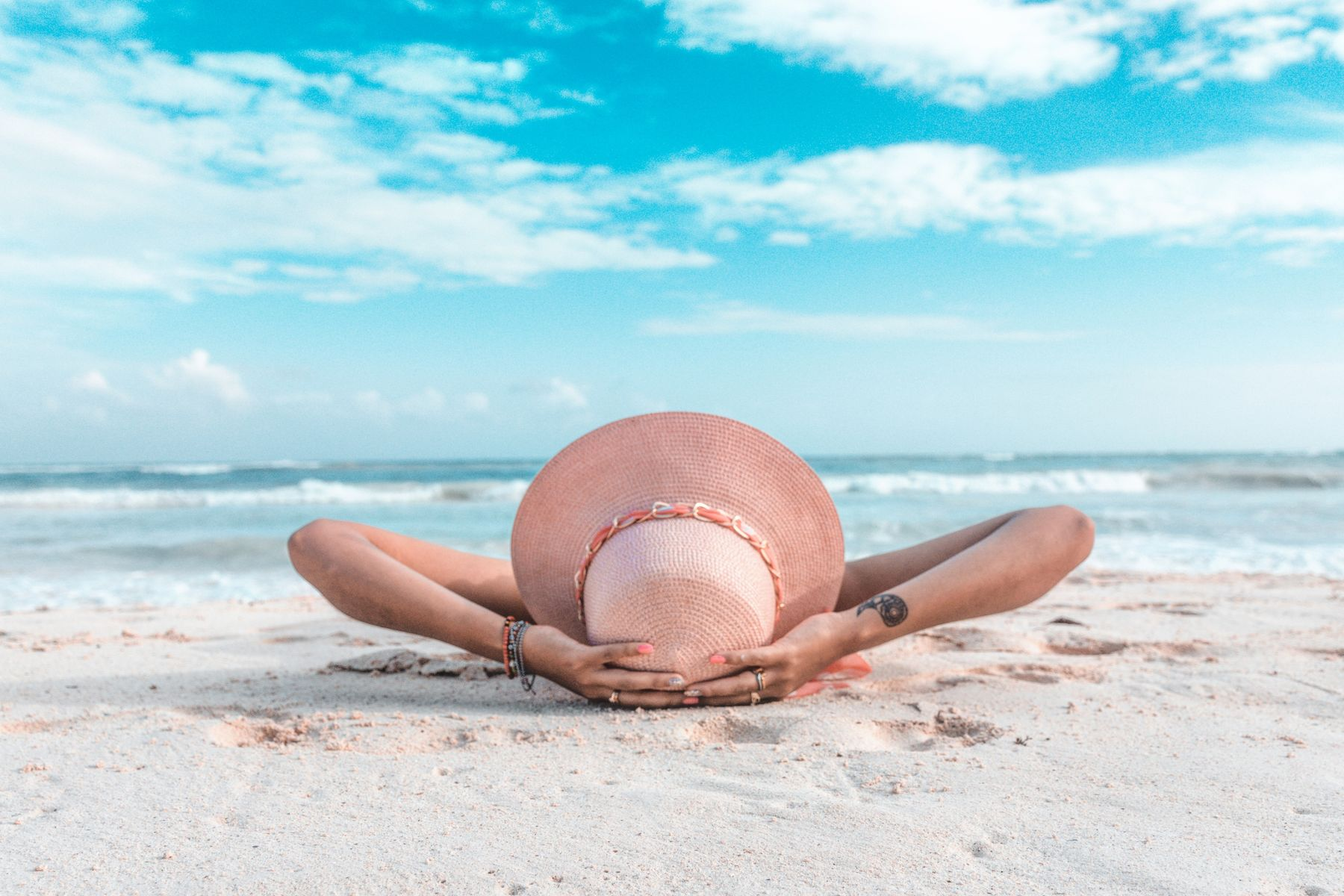 person with a beach hat on resting on the sand by the beach in Playa del Carmen, Mexico.