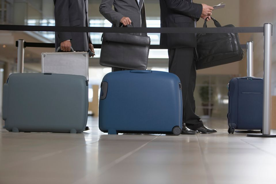 Businessmen at the airport check-in - 8 travel gadgets and accessories to keep your luggage safe