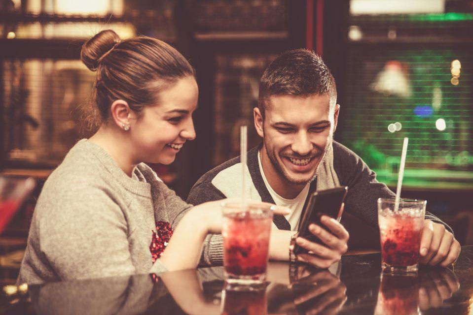 Χαρούμενο ζευγάρι πίνει ποτό και τσεκάρει πράγματα στο κινητό