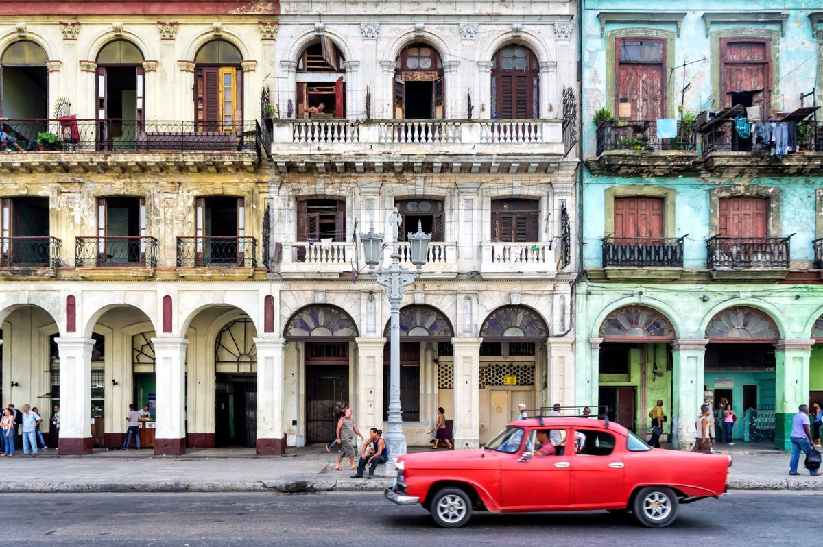 Красный винтажный автомобиль на фоне колониальных зданий в Старой Гаване.