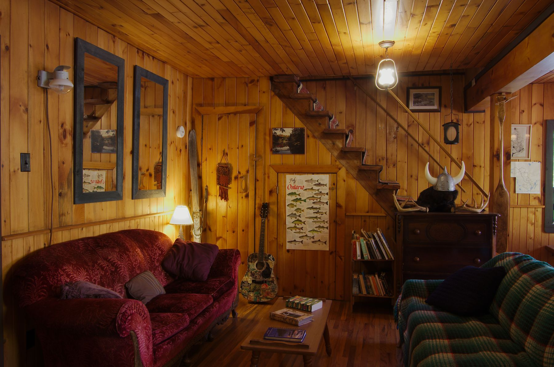 interior of algonquin eco lodge. a cozy living room with red couch, stairs, posters on wall