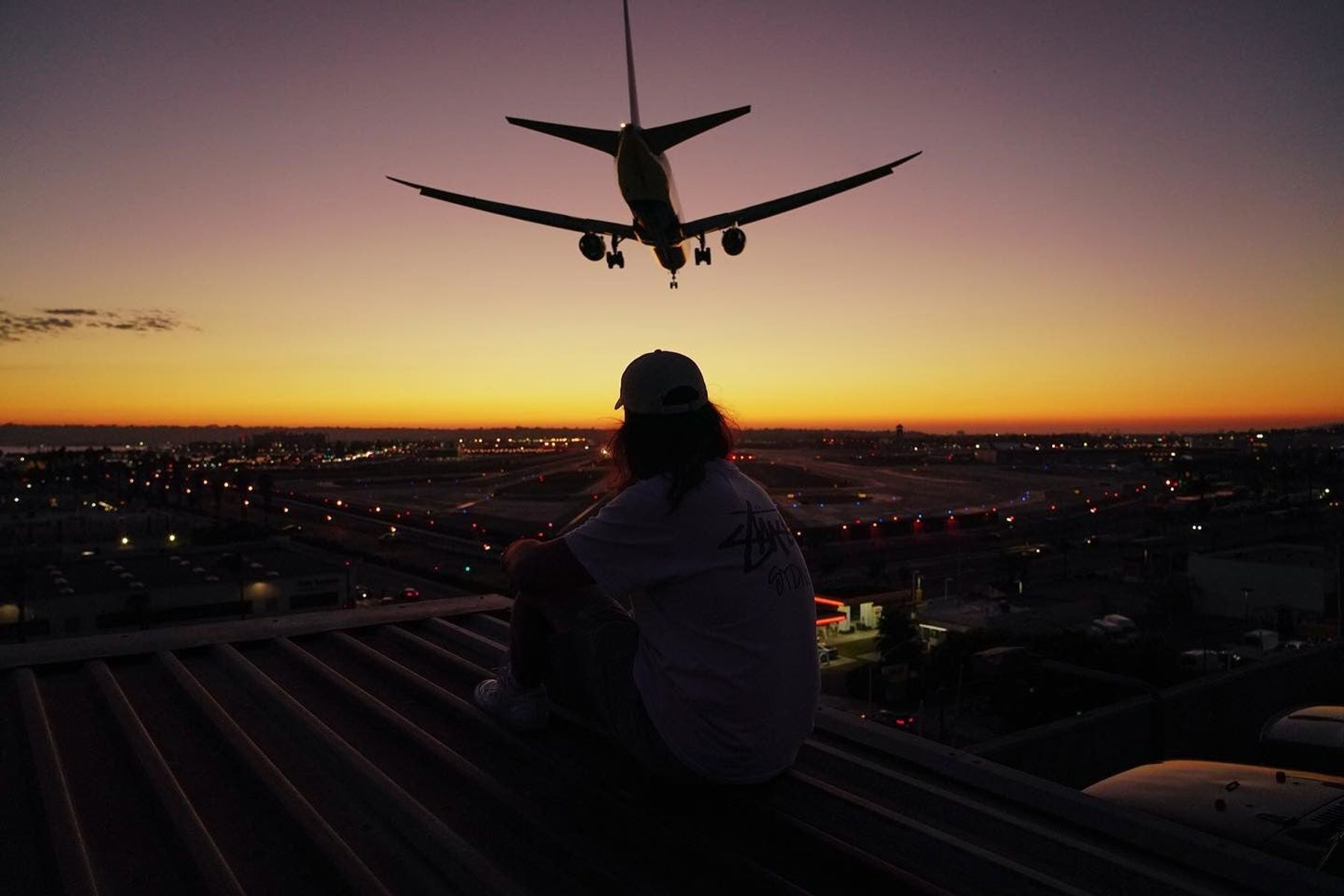 A person sits on a roof by an airport and watches a plane fly over, perhaps contemplating the future of travel.
