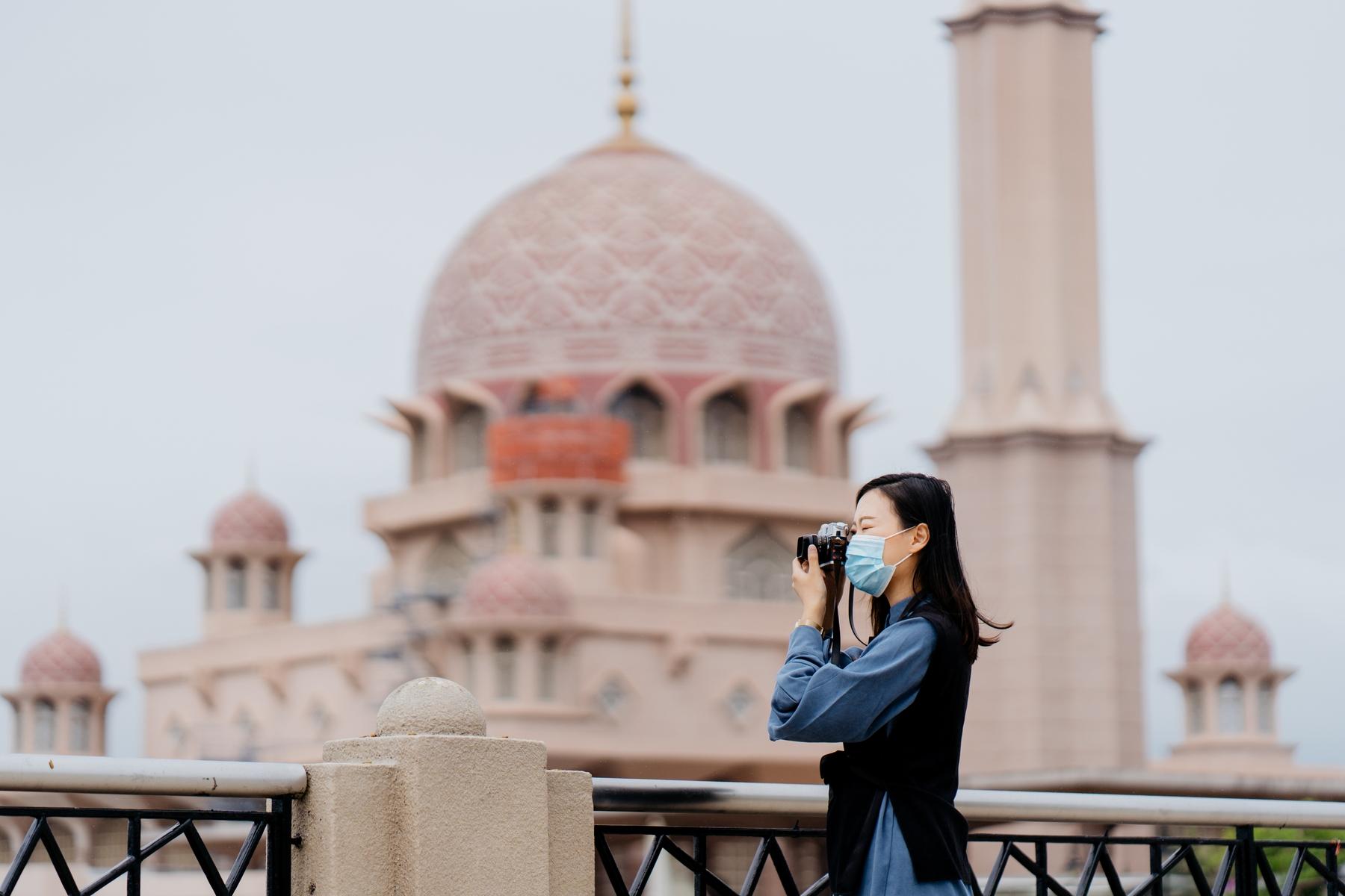 Jovem asiática de máscara fotografando um ponto turístico.