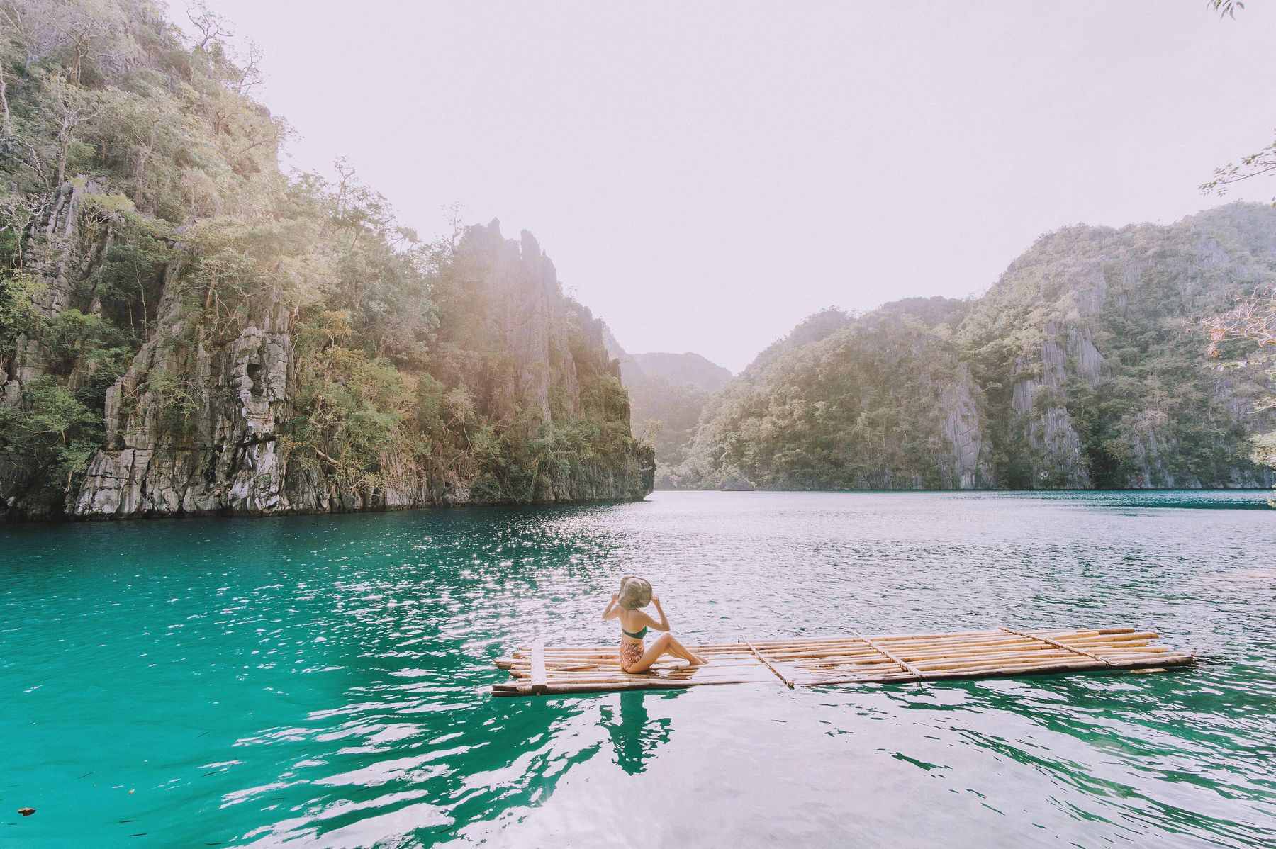 woman on a bamboo raft floating on a lake