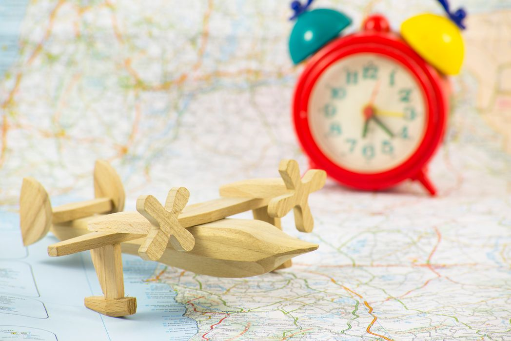 A wooden toy plane and a colourful clock on a map