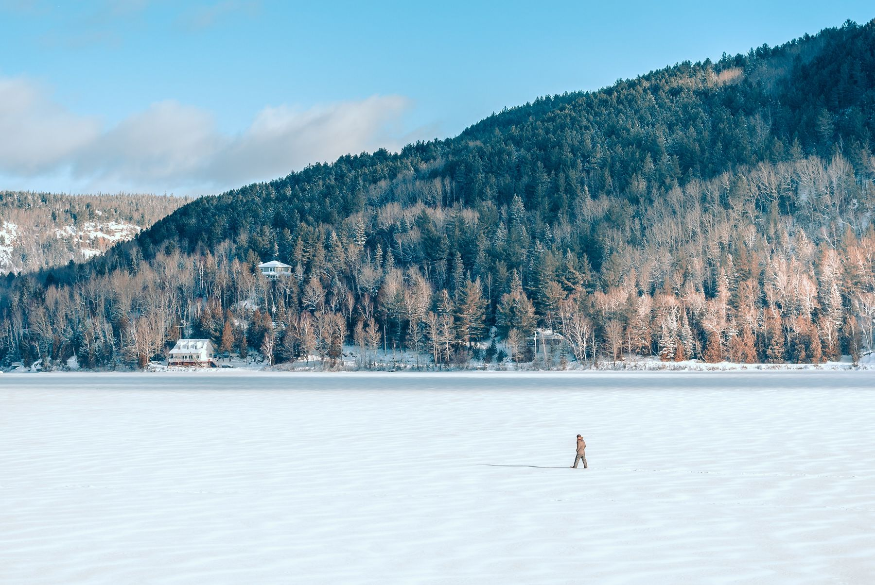 person walking on a frozen lake in Mont Tremblant, Quebec, on a sunny winter's day
