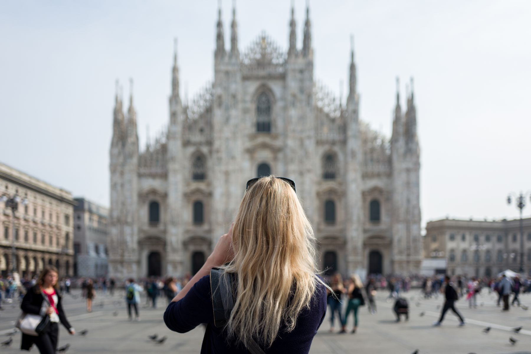 Female tourist taking a photo of the Duomo di Milano (Milan Cathedral) in Italy.