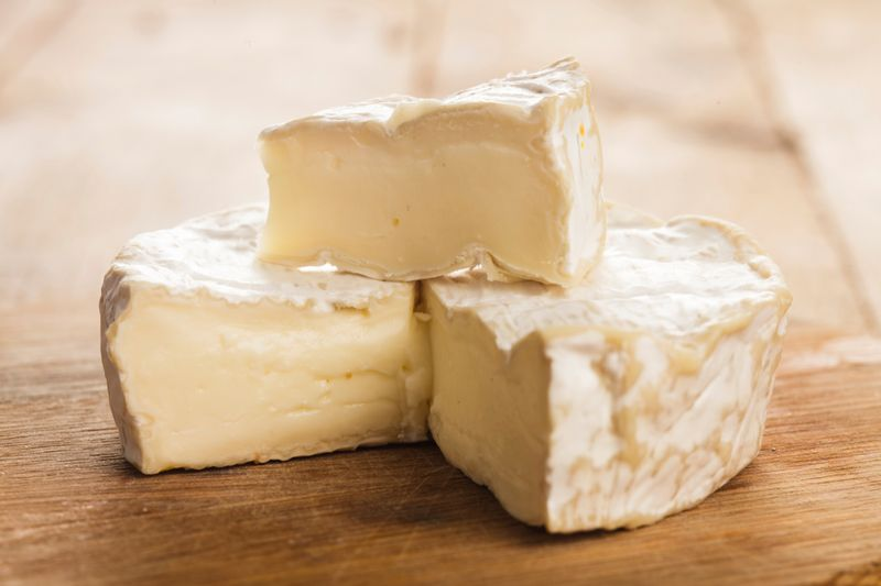 camembert cheese being cut